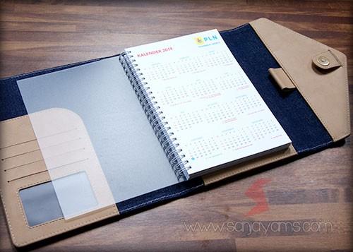Agenda promosi dengan bahan kulit cokelat kombinasi jeans